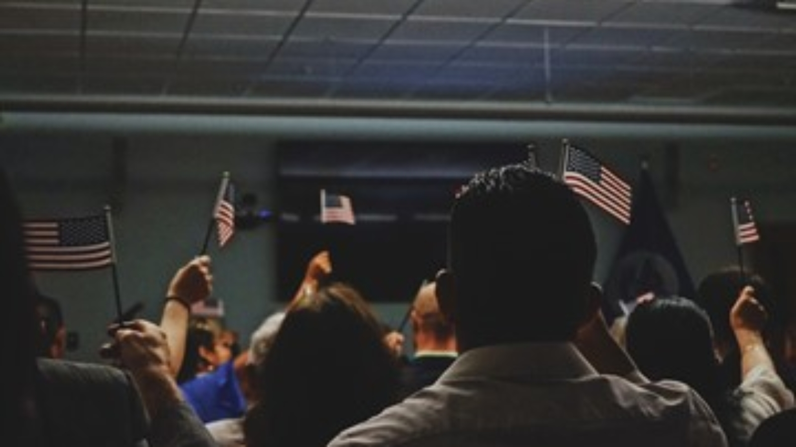 immigrants and non-citizens holding US flags at a conference