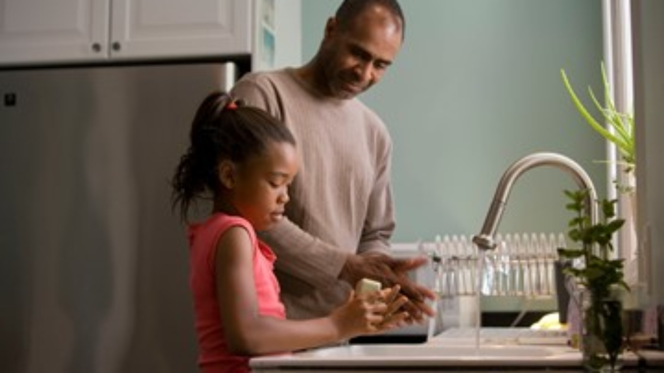 A father and daughter washing dishes together.